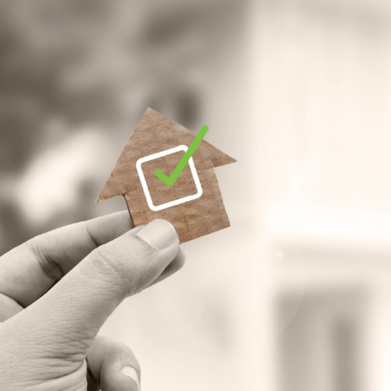 hand holding a house with a green checkmark