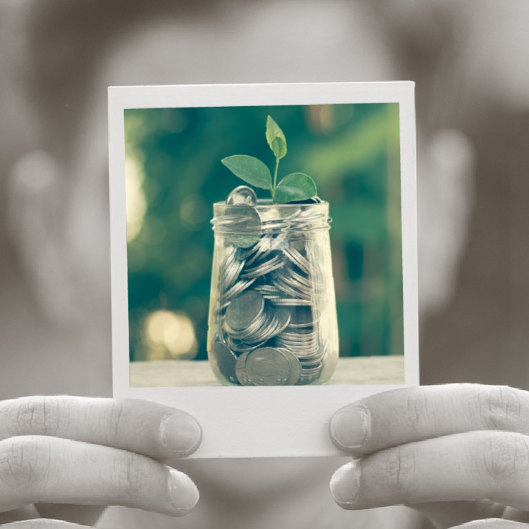 hand holding jar of money with a plant growing out of it
