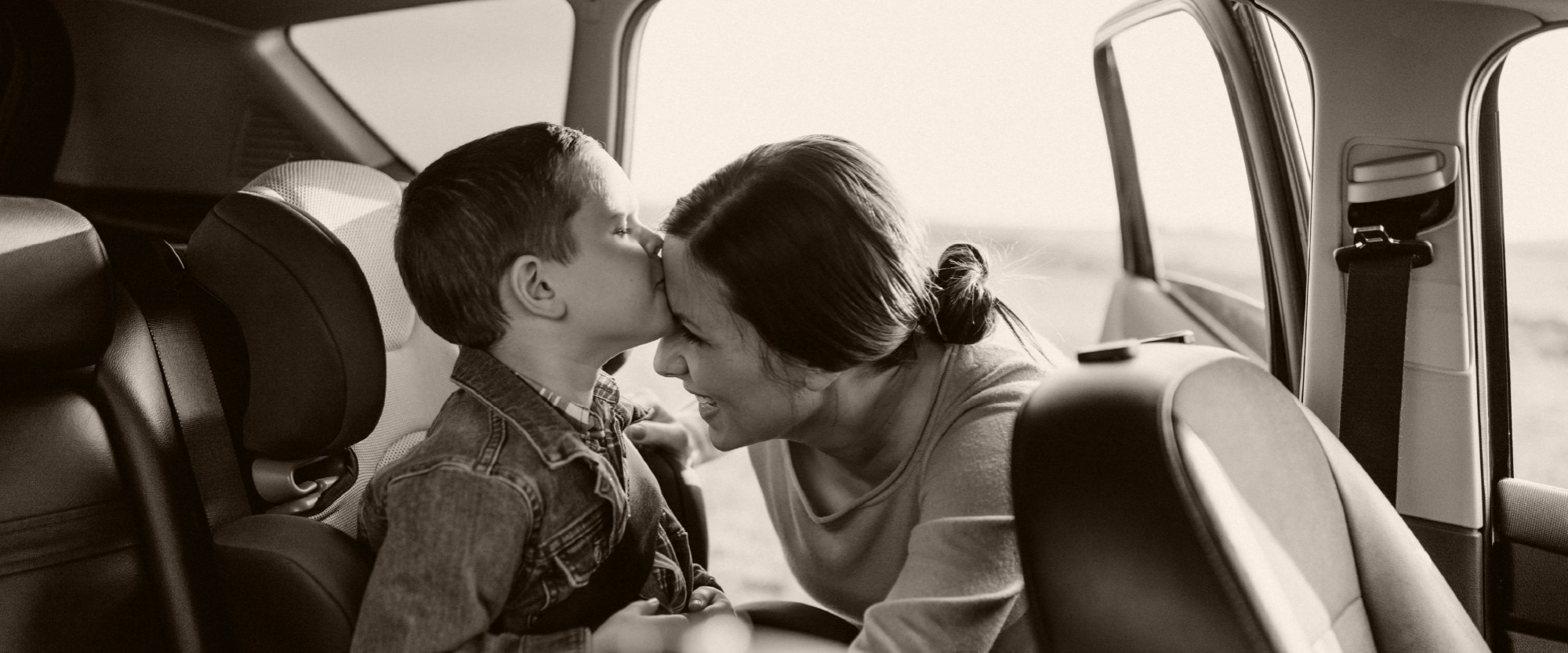 Photo of kid kissing mom after being buckled into car seat in back