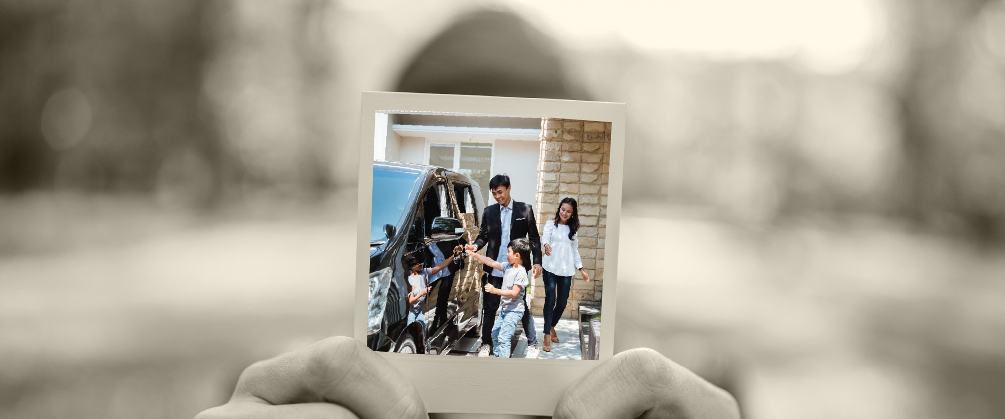 polaroid of family getting into a car on driveway of their home