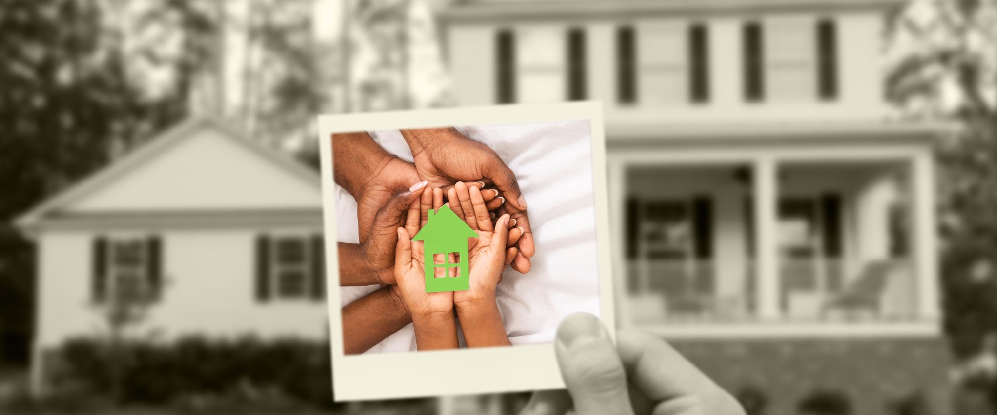 polaroid of two adults and child's hand holding a green cutout of a home in their palms against the backdrop of a house