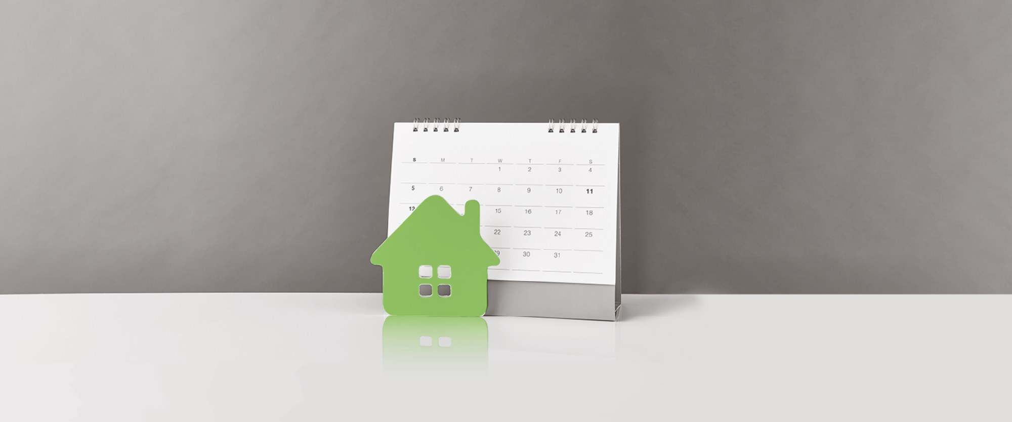 a green paper house in front of a calendar