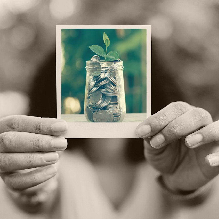Woman holding a polaroid photo of a jar of quarters