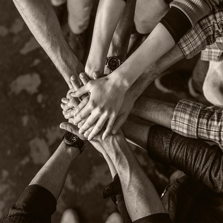 Group of people in a circle with hands stacked on top of each other
