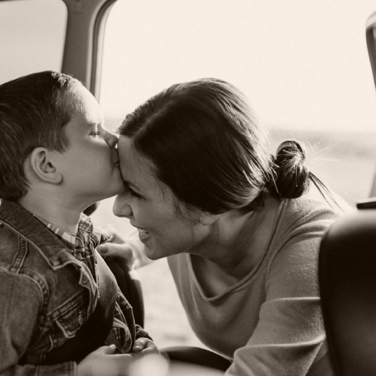 child in backseat kissing mom on cheek after being buckled in